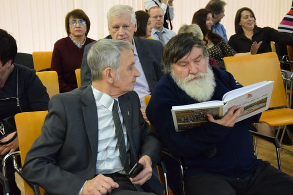 "Валерий Хилтунен (справа) разглядывает книгу, изданную к юбилею ""Товарища"""
