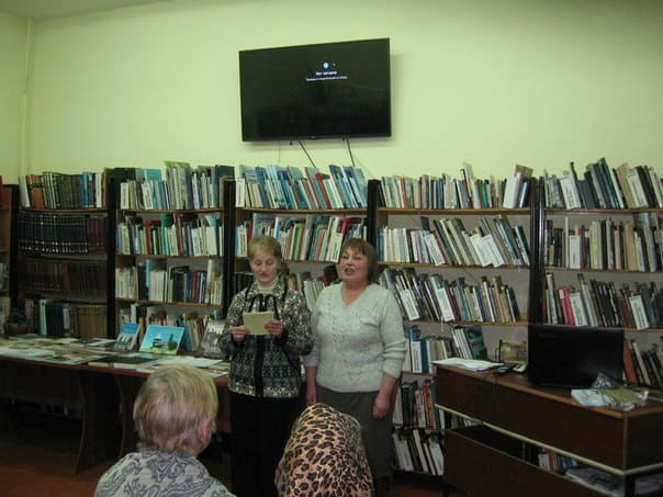 Читатель библиотеки Т.Ф. Захарова и автор книги, библиотекарь Е.П. Романова поют песню о Кажме - своеобразный гимн родной деревне