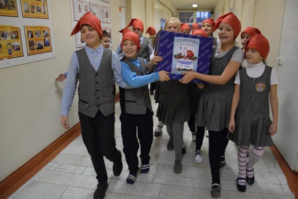 Школьники несут посылку со своими поделками