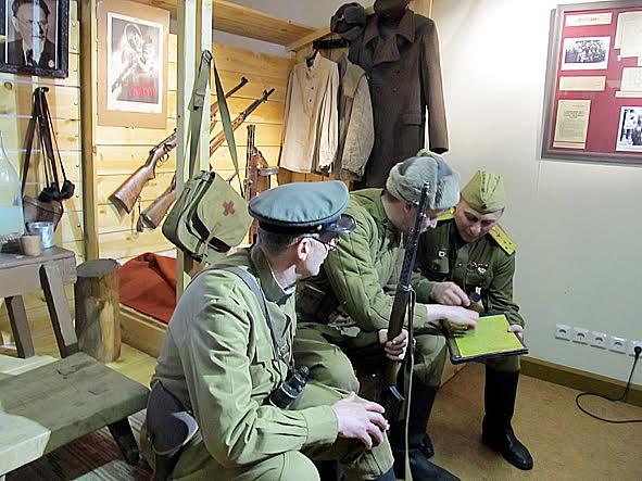 Представители выставочного центра «Полет» на фоне условной базы партизан. Авторы выставки реконструировали ее с помощью предметов из собрания этого центра