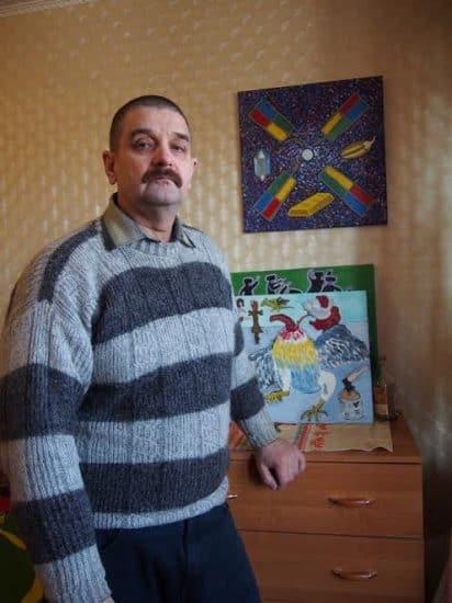 Юрий Рыбкин на фоне своей картины, посвященной мельнице Сампо