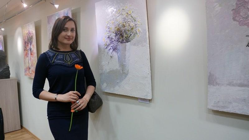 Живописец Жанна Свиридникова на фоне экспозиции своих новых работ