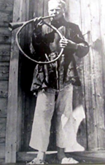 На старой фотографии один из исполнителей демонстрирует как играли на «Трубе колесом»