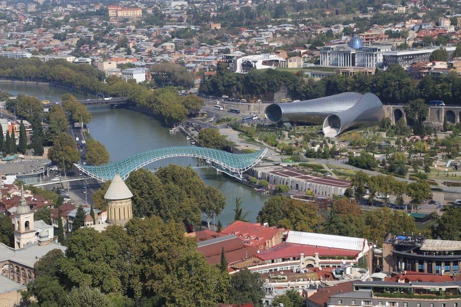 Вид на город сверху, куда мы поднялись на фуникулере. В центре современный мост Мира. По нему любят прогуливаться туристы. Вечером он сияет всеми цветами радуги