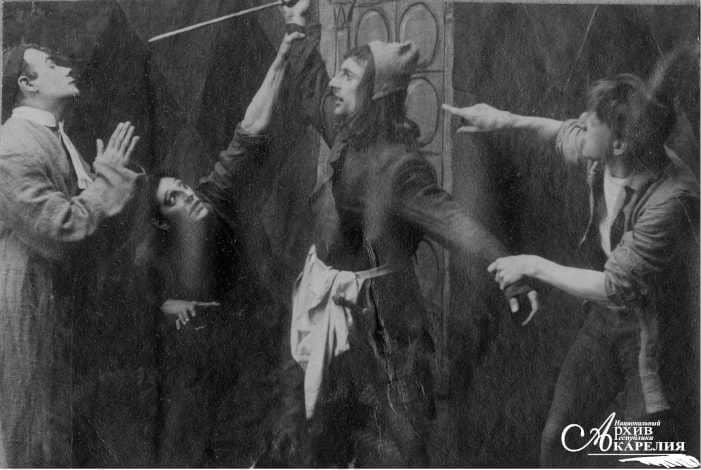 Сцена из спектакля по произведению Ганса Сакса «Уленшпигель со слепцами» в исполнении труппы Мурманской железной дороги под руководством Г.Ф. Гнесина. Слева направо: Г.Ф. Гнесин в роли пастора, [С.]Д. Хрусталев, В.И. Катун в роли кабатчика.  Петрозаводск. Май 1918 года. «Народная фотография» Петрозаводска
