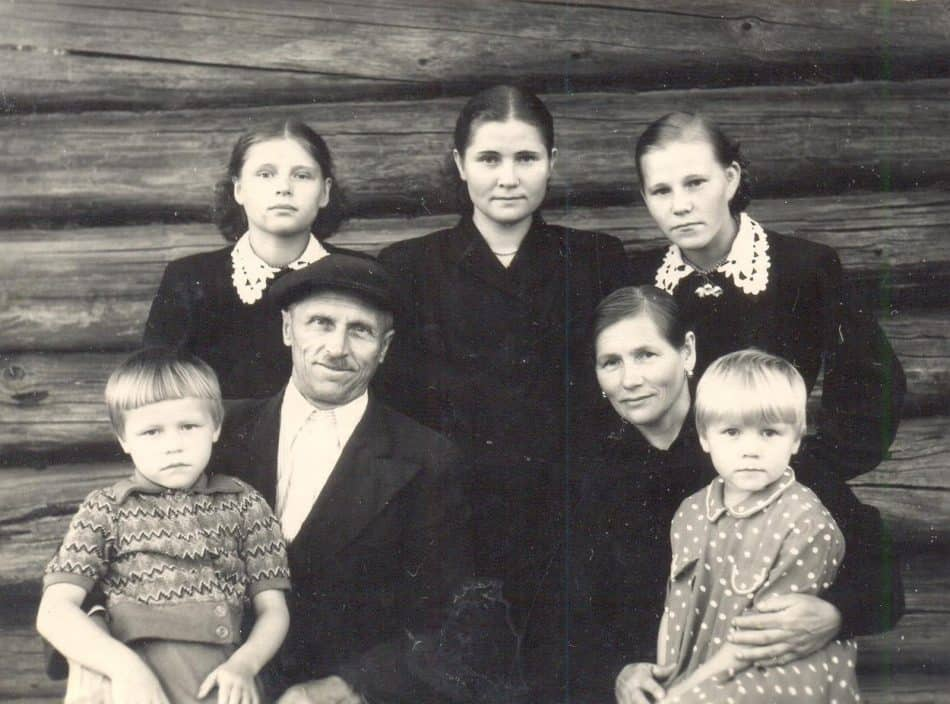 1 ряд: Папа Иван Андреевич с Лидой на руках, мама Иринья Дмитриевна с Валей на руках. 2 ряд: я, старшая сестра Людмила, моя подруга Нина Ваганова. Великая Губа, 1955 год