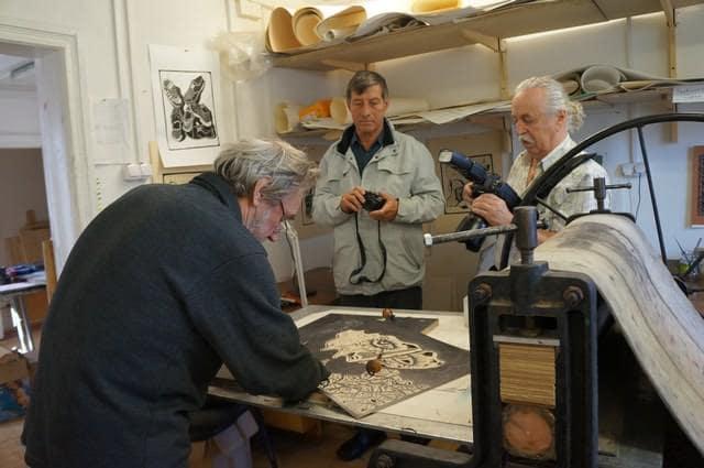 Финские фотографы побывали в Графической мастерской Петрозаводска. Известный карельский художник Аркадий Морозов показывает гостям свое  мастерство техники линогравюры
